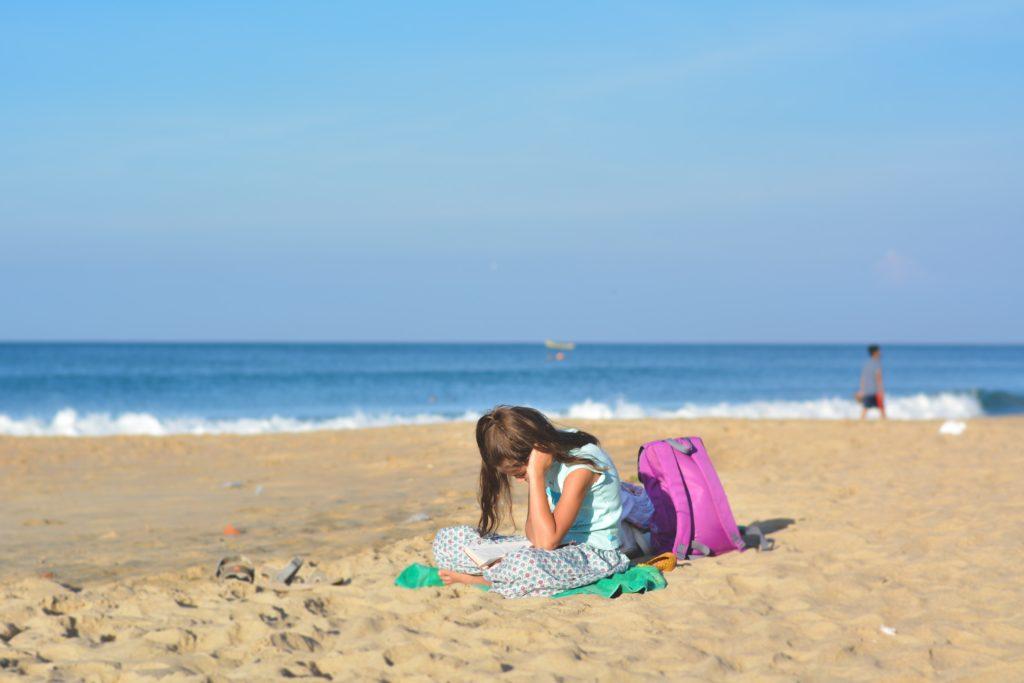Un fille absorbée par son bouquin sur la plage : ça c'est de l'immersion !